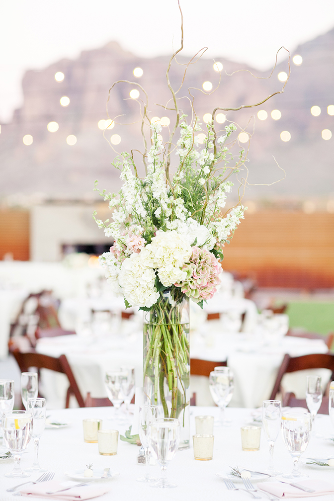 Outdoor wedding reception decorated with flowers and globe lights. Arizona wedding.