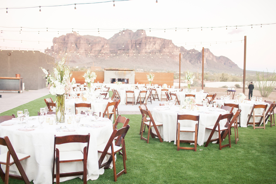 Outdoor wedding reception decorated with flowers and globe lights. Arizona mountain view wedding