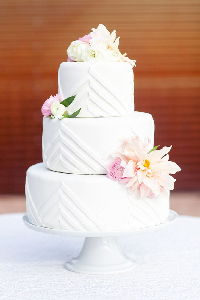 Modern, minimal wedding cake design with chevrons and fresh flowers.