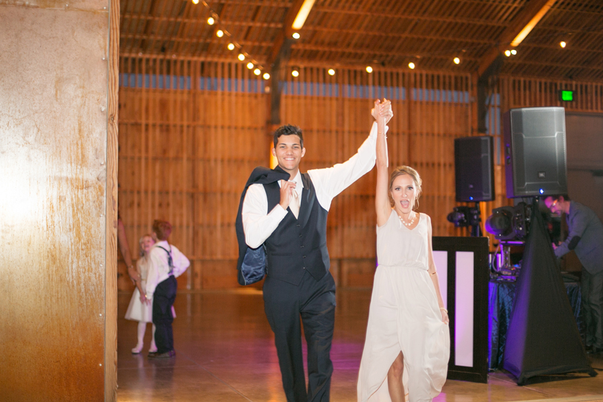 Bridesmaid & groomsman enter the reception with hands in the air. Wedding reception.