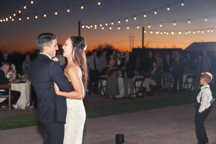Bride & groom dance at their outdoor wedding reception as the sun sets. Arizona wedding.