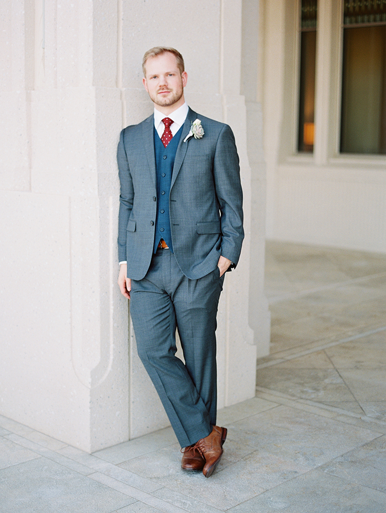 groom in a gray suit and red polka dot tie