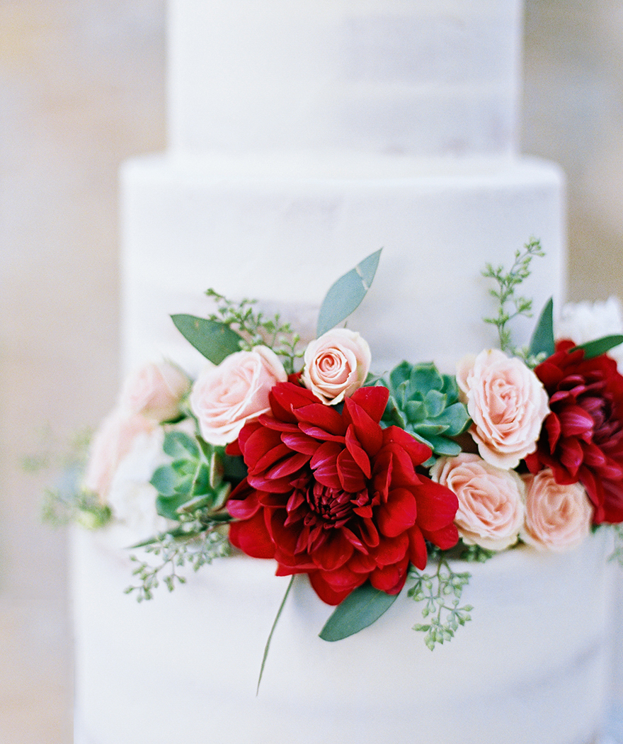 white almost-naked cake with red and pink flowers and succulents