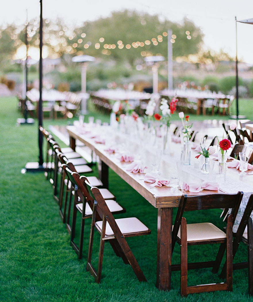 outdoor reception with wood table and chairs and string lights