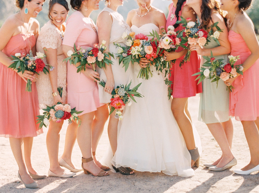 Pastel and bright bridesmaids laugh with bride and bouquet arrangements. Outdoor wedding.