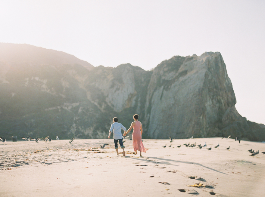 Couple running through the sand, engagement photo