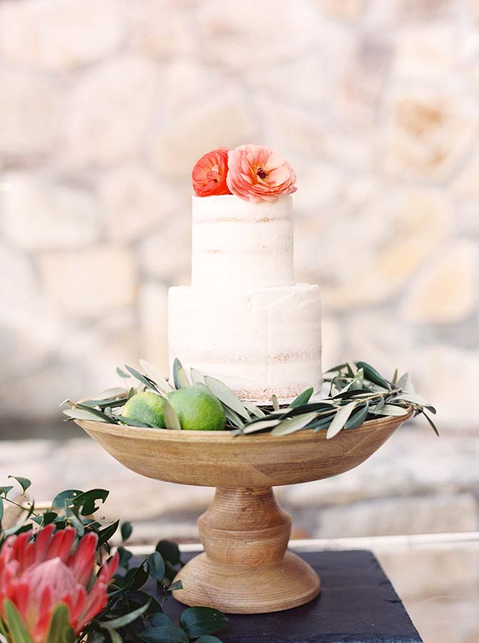 nearly naked wedding cake on a rustic wooden stand