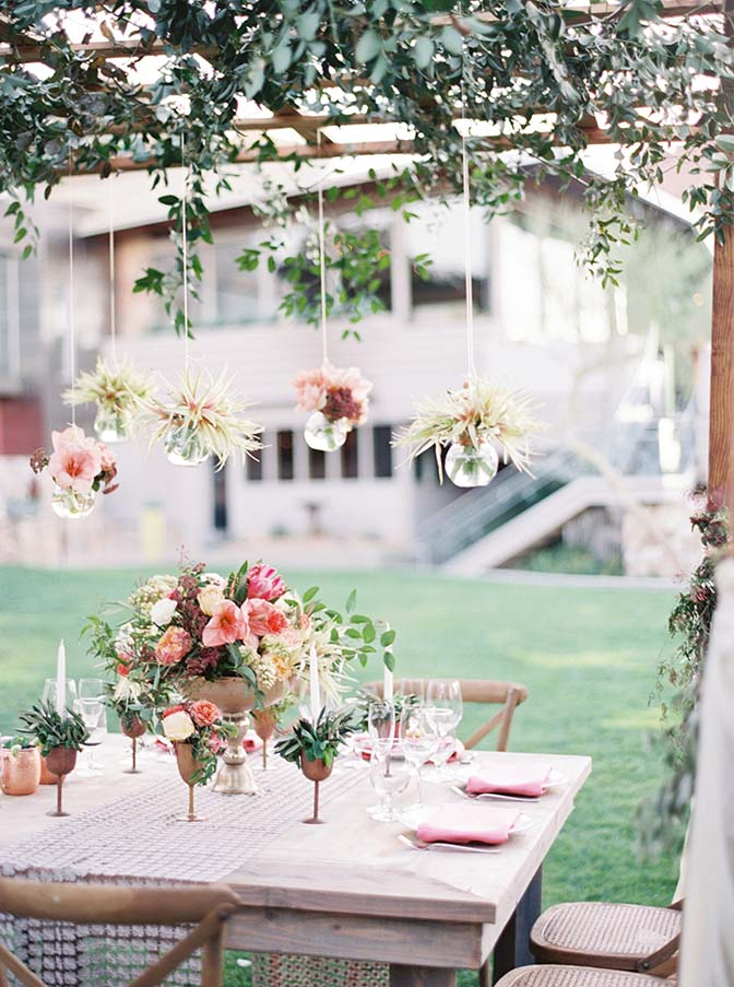 dreamy outdoor reception with suspended vases of flowers and succulents