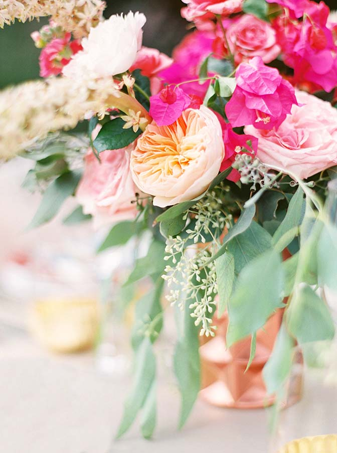 vibrant outdoor reception with pink flowers and metallic accents