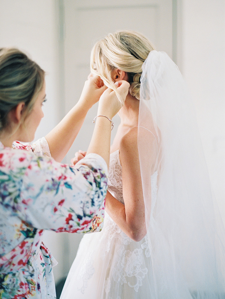 bridesmaid helps with the finishing touches