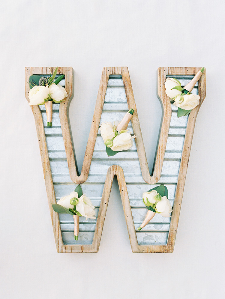 fun metal letter decor displays groomsmen's boutonnieres