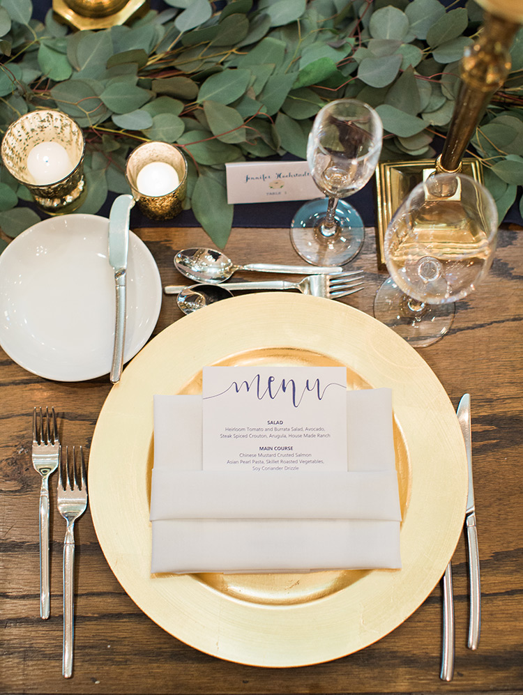 modern wedding reception with greenery and gold accents