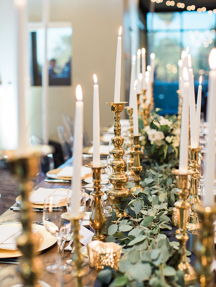 candlelit wedding reception with greenery and gold accents