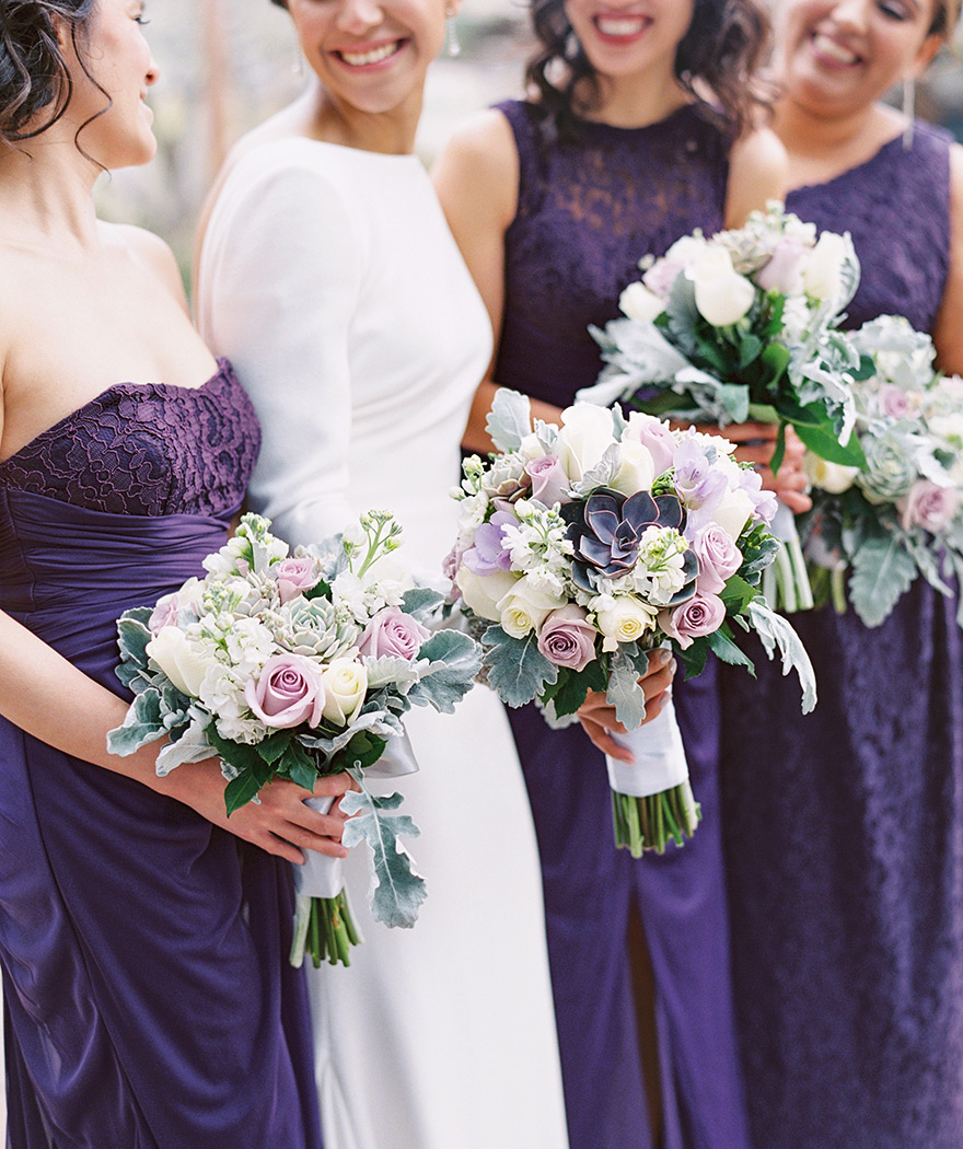 Bridesmaids in rich purple, pale bouquets with succulents