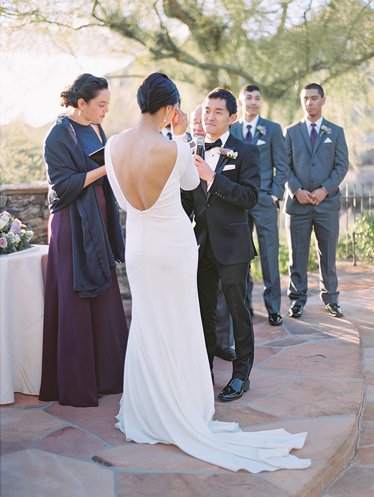 Exchanging vows, backless wedding dress