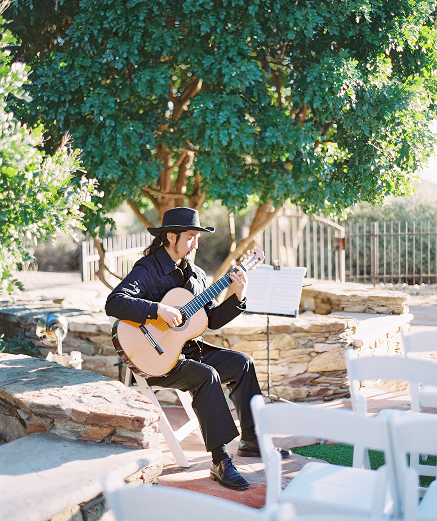 Miguel de Maria plays guitar for an outdoor wedding ceremony