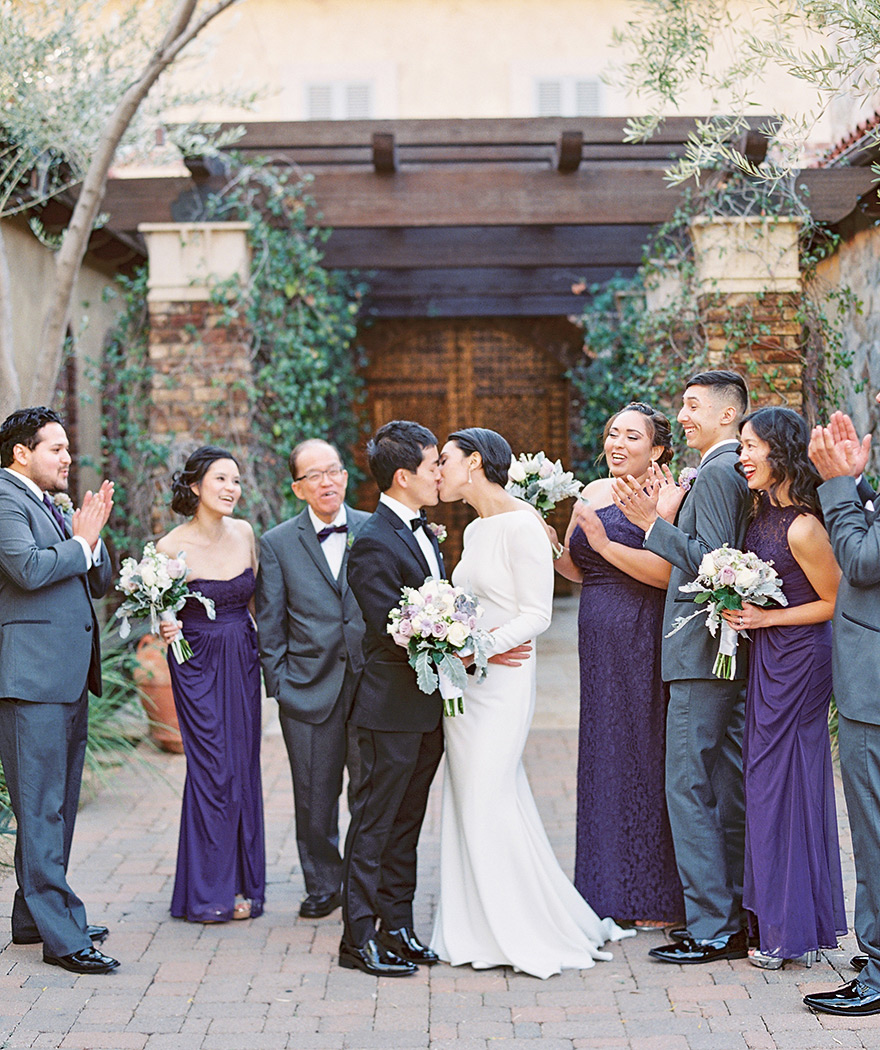 A kiss between the stylish bride & groom, bridal party in purple