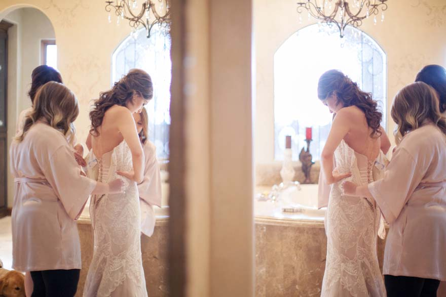Mirror view of the bride putting oner her dress