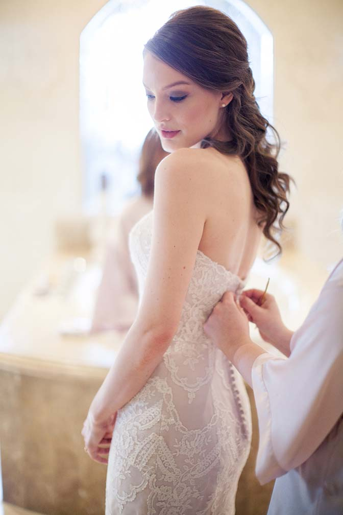 The final buttons being fastened - strapless lace Maggie Sottero dress