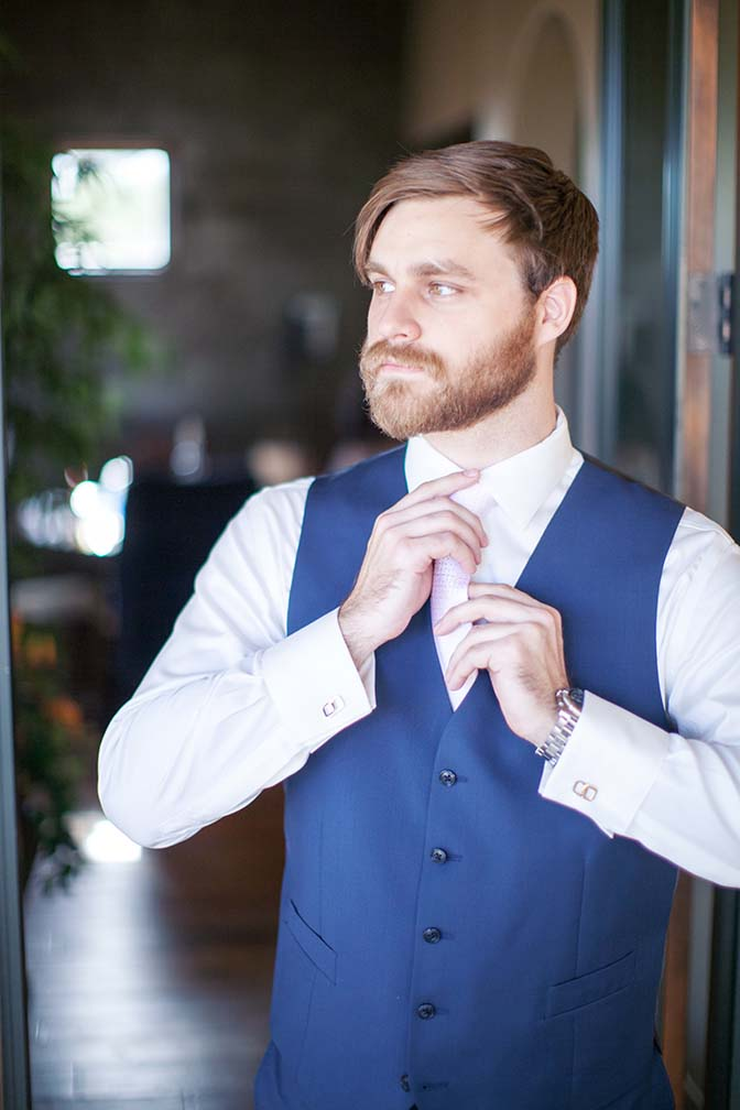 Bearded groom in a blue vest and pale pink tie