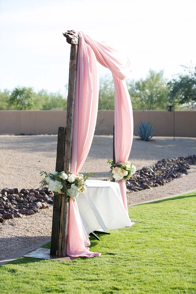 Wooden wedding arch draped in pale pink fabric