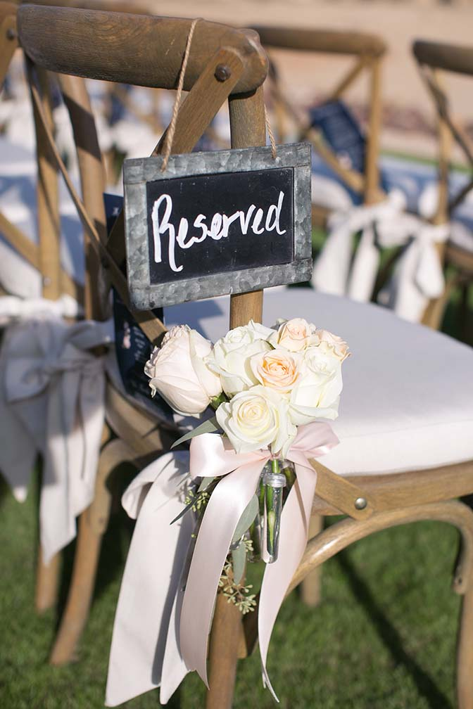 Wedding ceremony chair decorated with pale roses and chalkboard sign