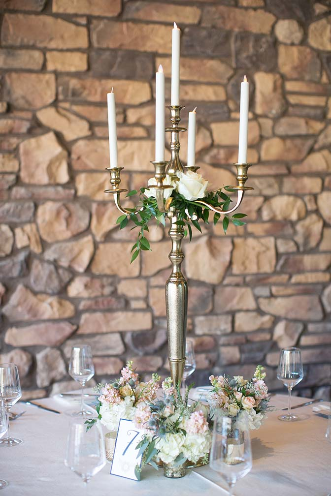 Brass candelabra and fresh flowers, outdoor wedding reception