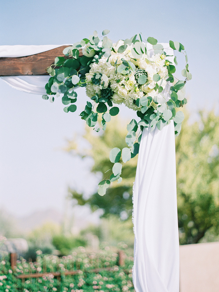 white flowers and fresh greens on a wedding arbor