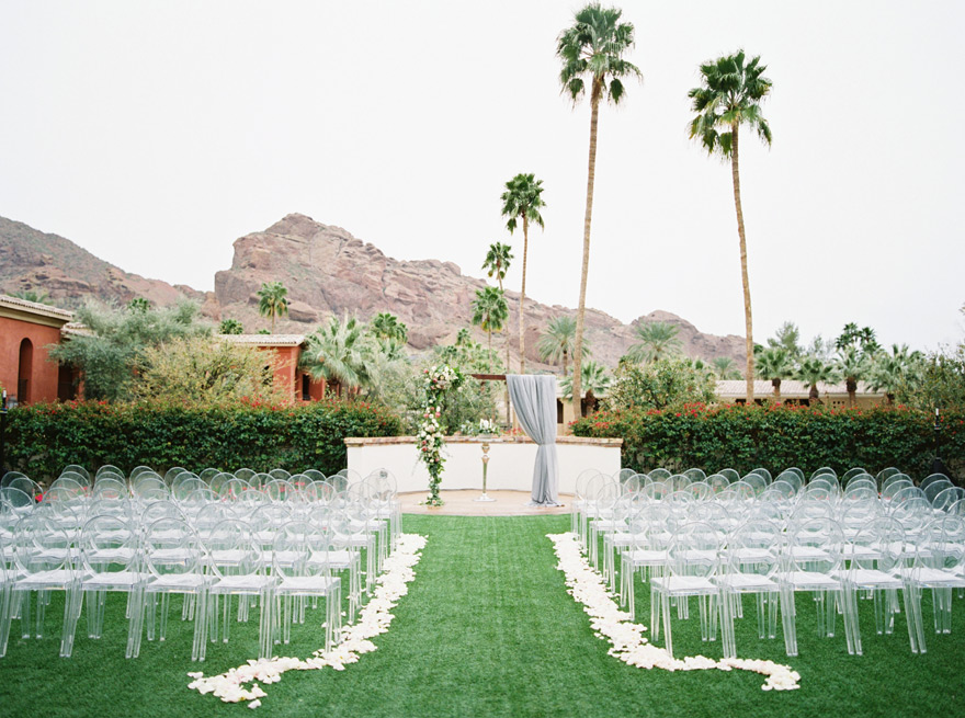 outdoor wedding ceremony with ghost chairs