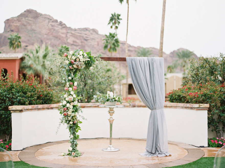 wedding arch with flowers and draped fabric