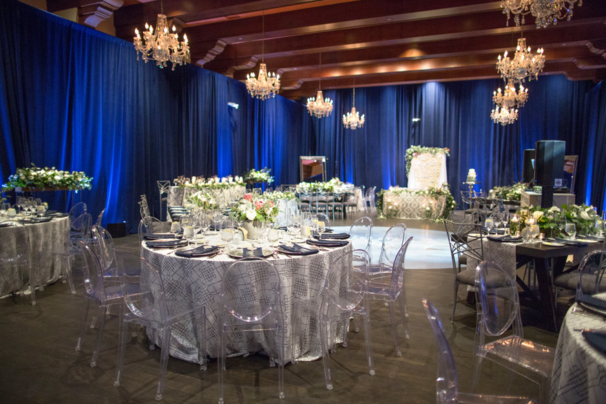 wedding reception with blue draped walls and ghost chairs
