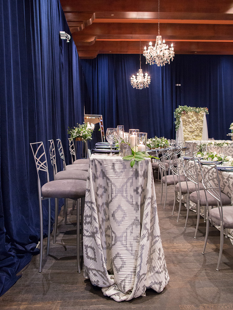 wedding reception with blue draped walls and chandeliers