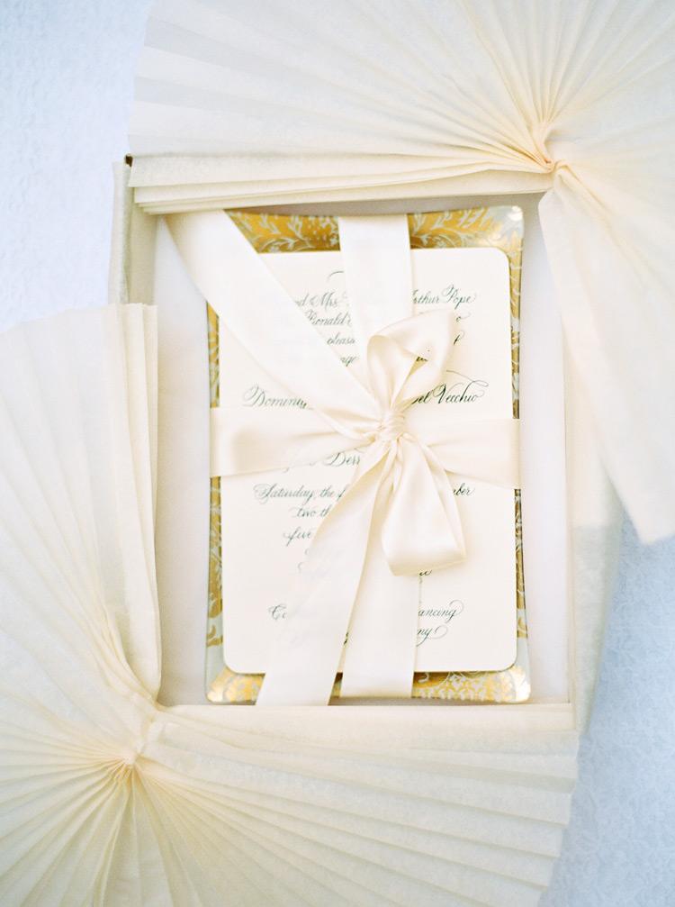 Cream satin wedding invitation. Elegant bow arrangement.