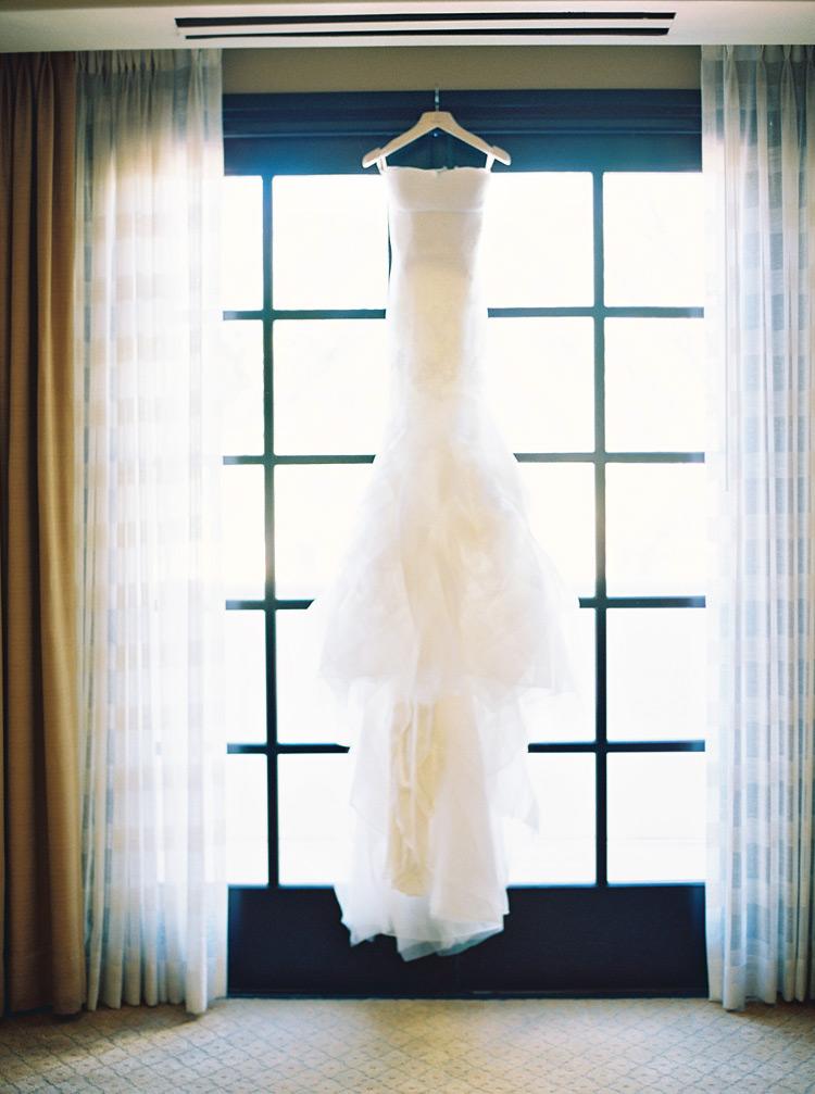 Hanging layered wedding dress from window seal.