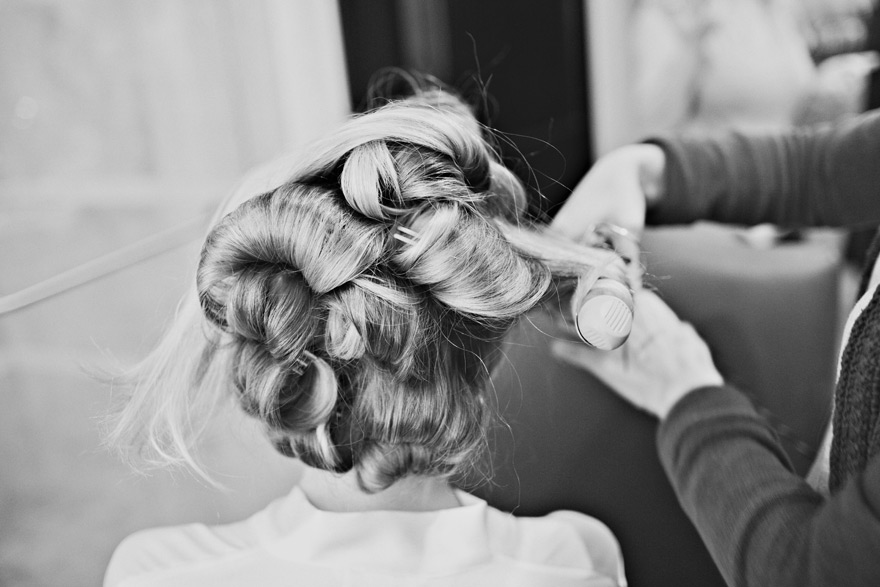 Bride getting her hair curled by stylist on wedding day preparation.