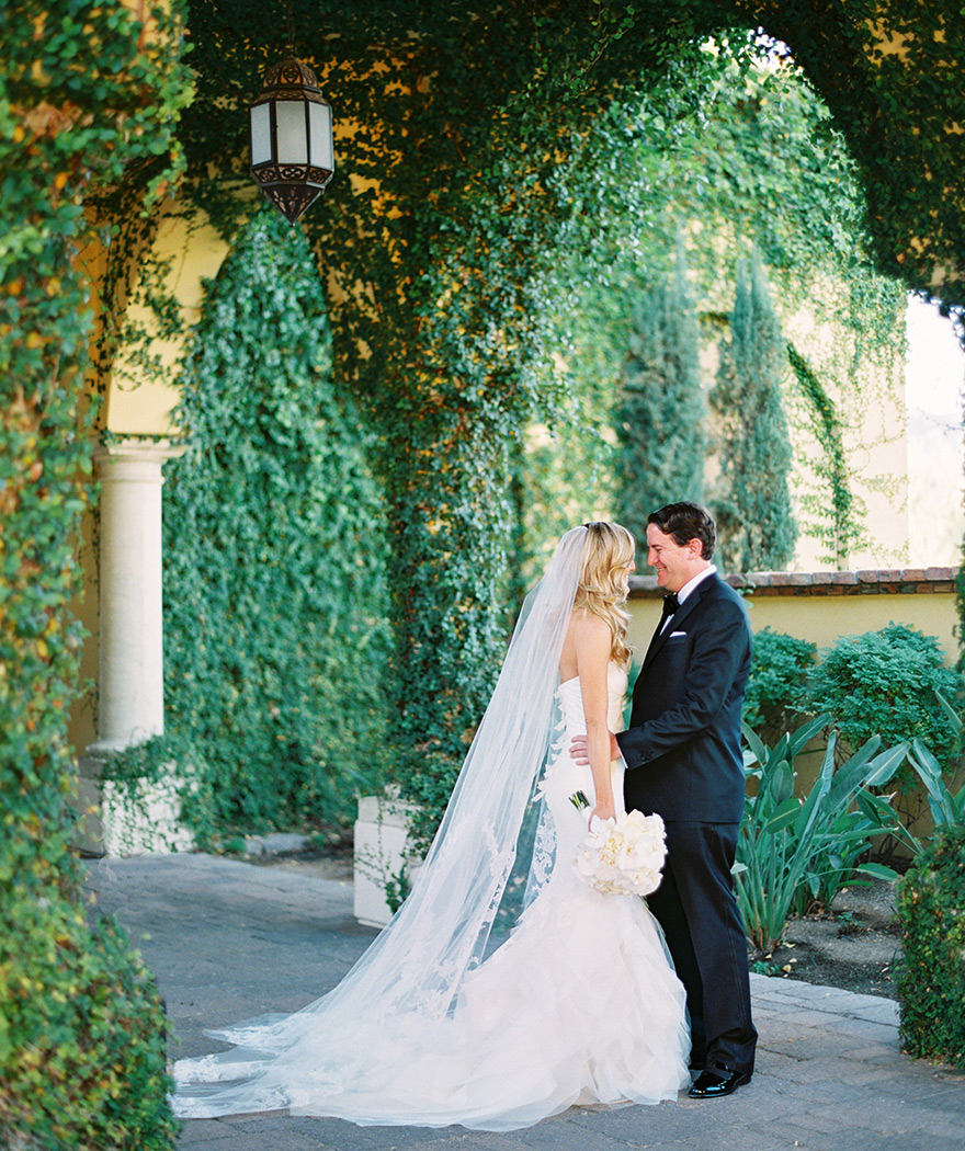 Bride and groom smile sweetly for the first-look session. Arch greenery tunnel scenery.