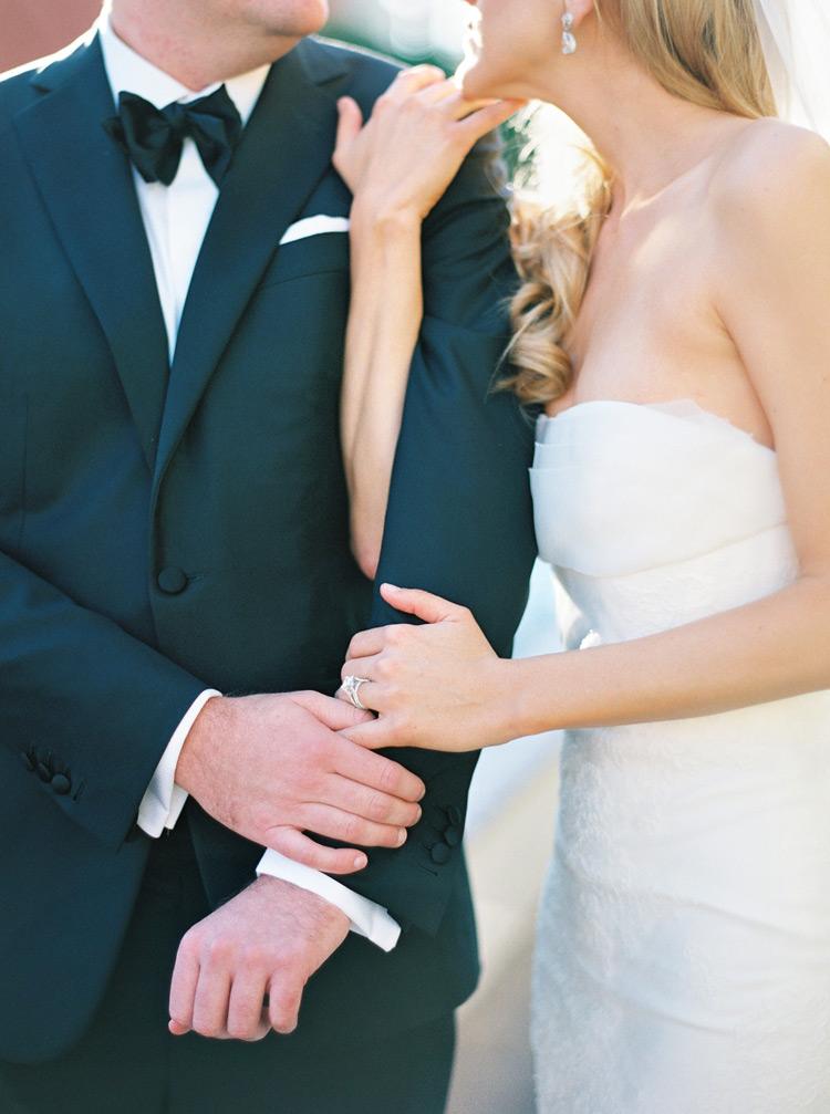 Bride embraces groom while holding arm in arm. Elegant outdoor Scottsdale wedding.