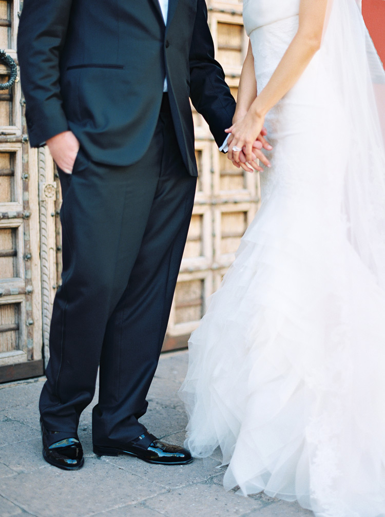 Bride and groom hold hand in hand in silhouette tulle dress. Scottsdale elegant outdoor wedding.