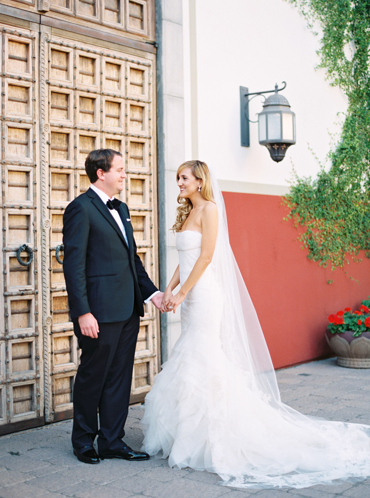 Bride and groom smile softly by wood layered door. First look outdoor session.
