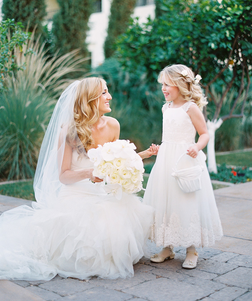 Bride and flower girl smile sweetly next to each other while holding holds. Scottsdale wedding.
