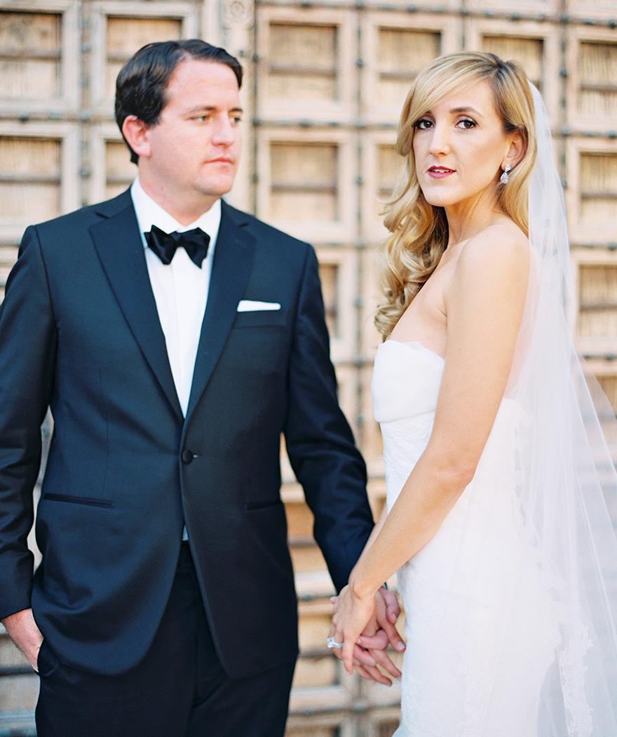 Groom looks at bride hand in hand while bride poses. Elegant Scottsdale outdoor wedding.