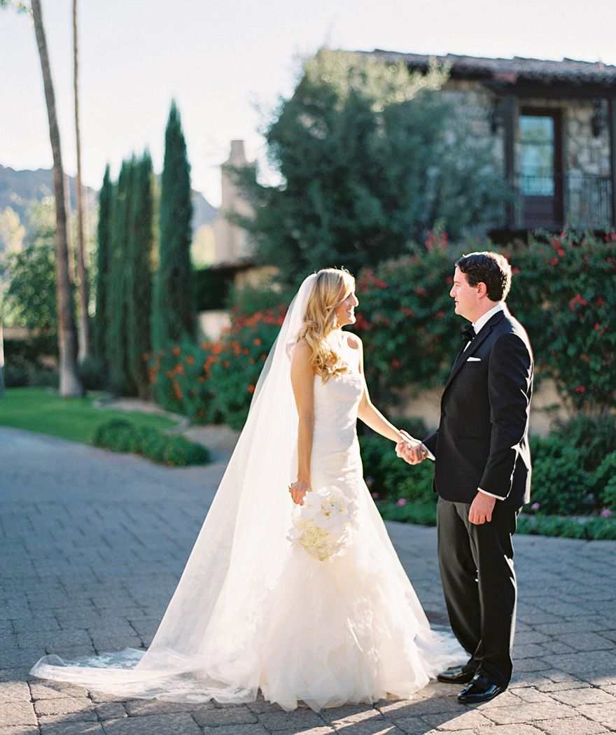 Bride and groom take hands while sharing a quick moment. Scottsdale Omni Montelucia wedding.
