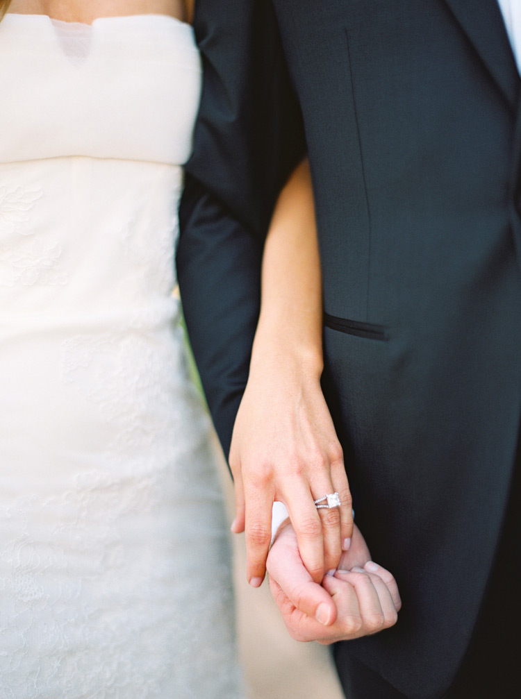 Bride and grooms hands intertwined with square wedding ring in place.