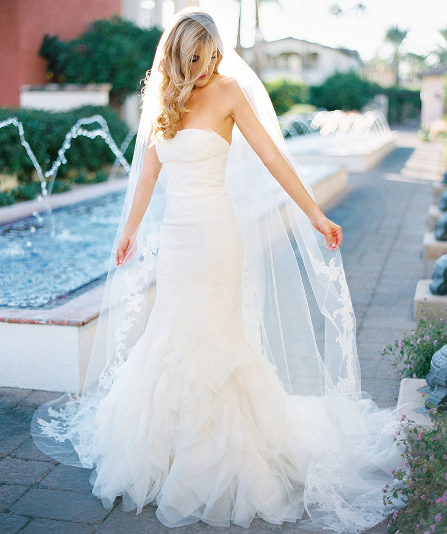 Blond bride holds long-train of veil next to fountain. Omni Montelucia wedding.