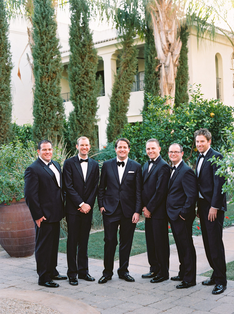 Groomsmen smile with groom. Outdoor green scenery.