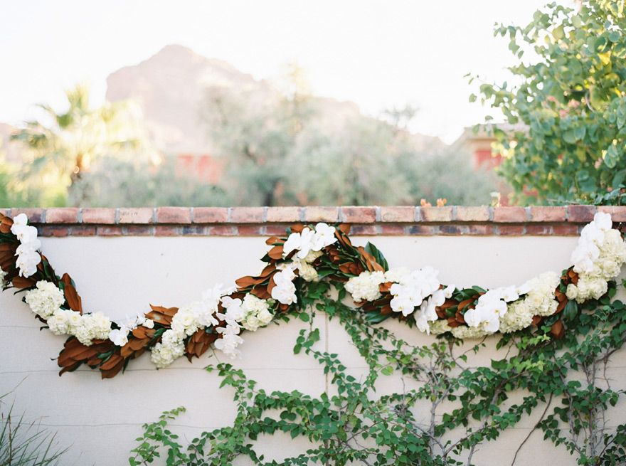 White orchid and brown leaf hanging wall decor. Outdoor Scottsdale wedding.