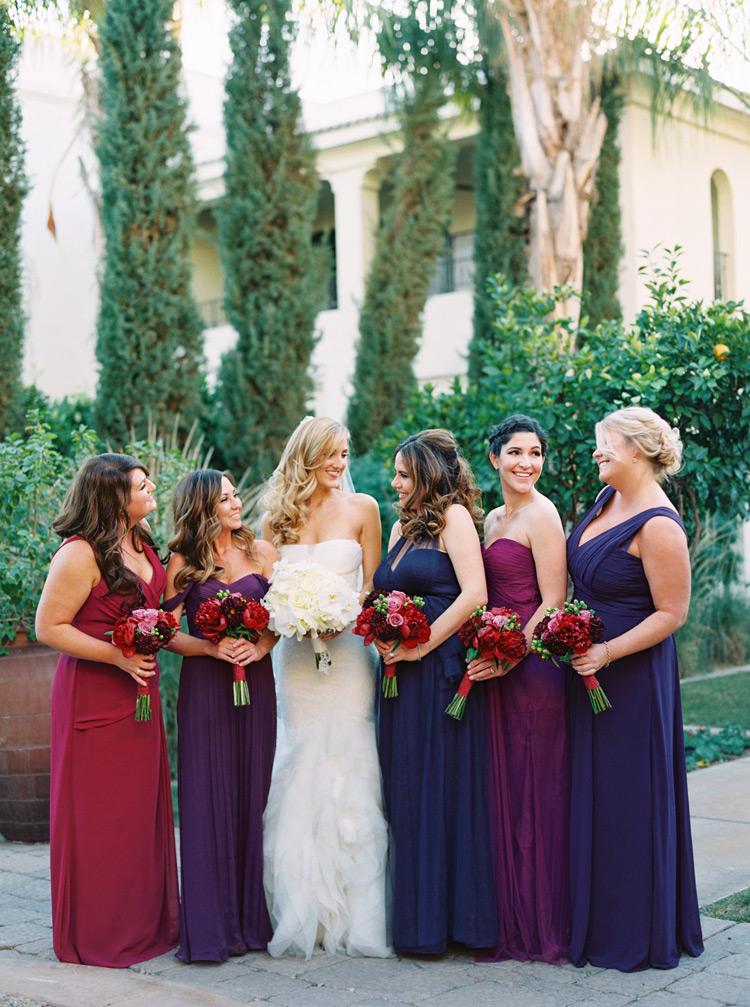 Bride smiling with rich colored, fuchsia bridesmaids.