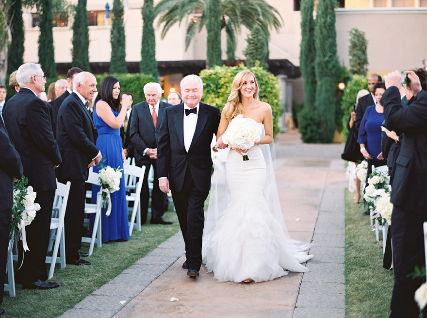 Smiling bride walks down aisle with father. Omni Montelucia weddings.