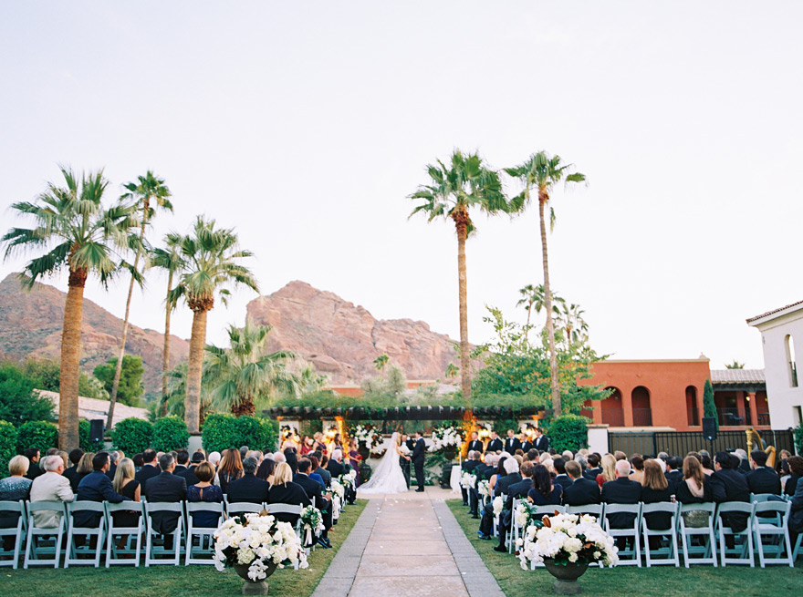 Guests watch bride and groom during ceremony procession of wedding. Outdoor Scottsdale wedding