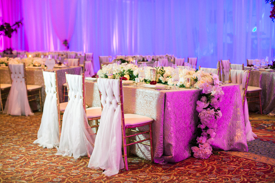 Elegant white and gold wedding table placement and chairs. Overflowing flower bundle.